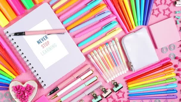Back to school or workspace colorful stationery overhead on pink flatlay.