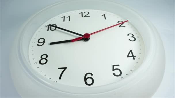 Devět hodin čas zahájení práce, uzavření bílé nástěnné hodiny na bílém pozadí, čas ukončení hodin chůze 15 minut.