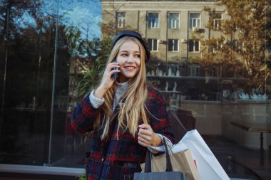Happy woman talking by smartphone and holding shopping bags