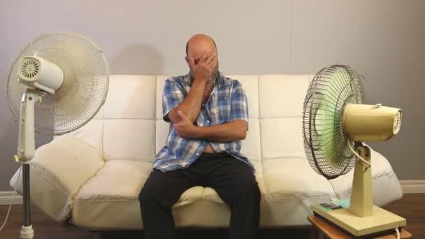 ein hitzegeplagter Mann sitzt vor zwei elektrischen Ventilatoren.