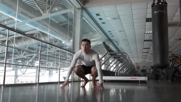 Ein junger Asiate trainiert im Kickbox-Fitnessstudio. aufwärmen. Kickboxer-Athlet wärmt sich aktiv vor hartem Training im Fitnessstudio mit verschiedenen Muscheln