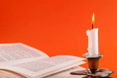 Mum yakma ve arka planda açık kitap portakalda izole edilmiş.