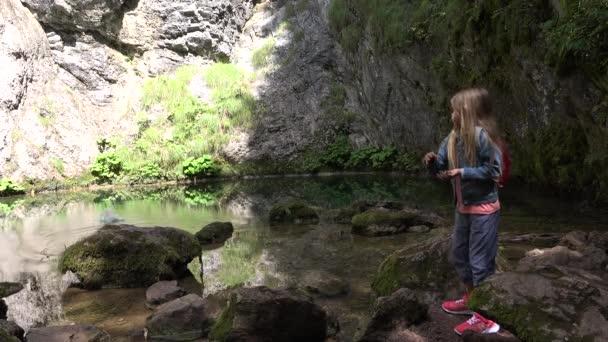 4 k Mädchen spielen durch ein Gebirgsfluss werfen Kiesel im Wasser, Kind im freien