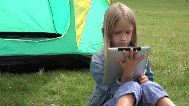 4 k gyermek játszik tabletta kemping sátor, a lány szörfözés szerkentyű, réten fű