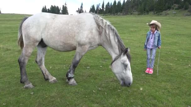 4k verängstigtes Kind von Pferd, Bäuerin mit Cowboyhut auf der Weide in den Bergen