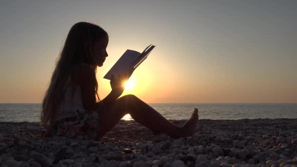 4k Mädchen lesen Buch am Strand, Sonnenuntergang Blick auf die Küste, Kind an der Küste