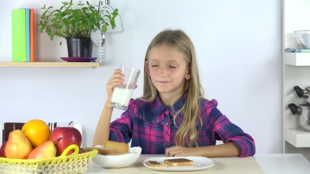Dítě pít mléko na snídani, dívka jíst chléb a čokoláda v kuchyni 4k