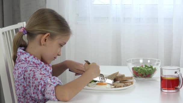 Dítě jíst vejce, hlávkový salát, ledový salát, dívka jí zelenina u snídaně 4k
