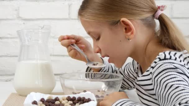 Dítě jíst mléko a cereálie na snídani v kuchyni, holka ochutnávka jídlo 4k