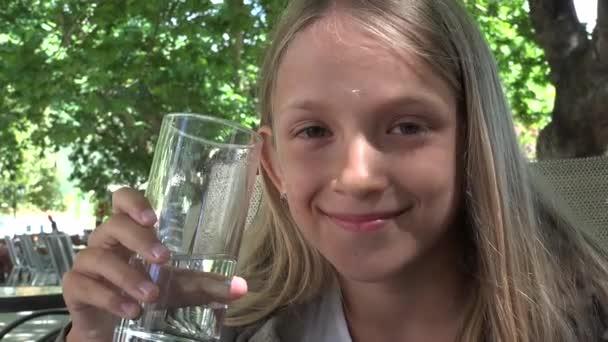 Kind trinkt Wasser im Restaurant, Kind hält ein Glas Wasser, Mädchen lächelt