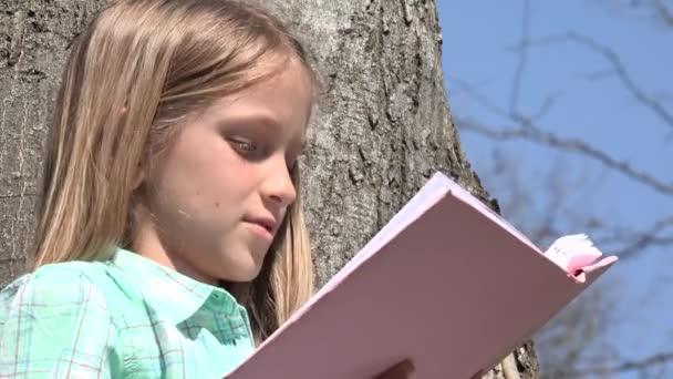 Gyermek olvasó-ban fa Park, iskoláslány elolvassa a könyvet kültéri, természet, nevelő