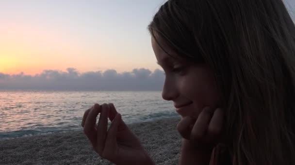 Dítě na pláži, chlapče, hraje na břehu v západu slunce, dívka sledování studiem oblázky