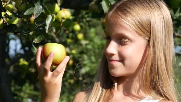 Farmář dítě v jabloňový sad, venkovská dívka ochutnávka ovoce stromu na vesnici