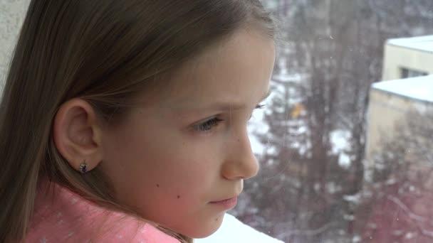 Dítě při pohledu na okna, nešťastný zamyšlená dívka tvář, sněží zimní den