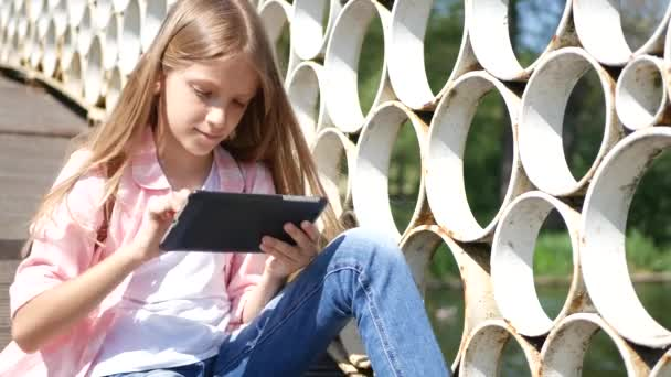 Child Playing Tablet in Park, Little Girl Uses Smartphones Outdoor in Nature
