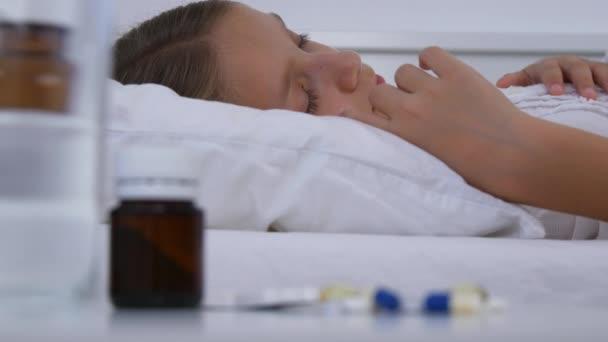 Krankes Kind schläft im Bett, krankes Kind schläft in Krankenhausmedizin-Pille
