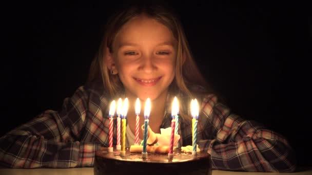 Soffiatura candele della festa di compleanno del bambino nella notte, Kid festeggiare con torta buio