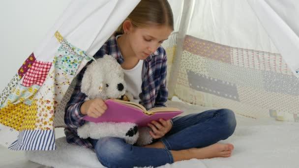 Bambino di lettura, studio nella sala giochi, del bambino giocare al parco giochi per bambini, apprendimento ragazza
