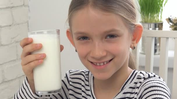 Dítě pít mléko k snídani v kuchyni, holka ochutnávka mléčných výrobků