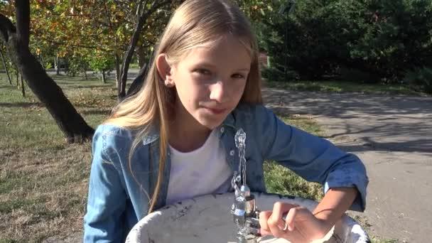 Kind trinkt Wasser aus öffentlichem Brunnen im Park, kleines Mädchen spielt im Wasser