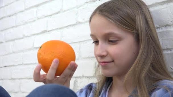 Kind isst Orangen Obst zum Frühstück, Mädchen Kind riecht gesunde Küche