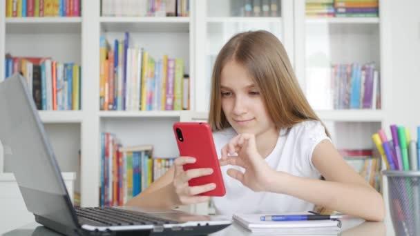 Kid pomocí Smartphone Studium ve videokonferenci, Učení dětí, Psaní v knihovně, Školačka chatování s učitelem doma v koronavirus pandemické krize, Domácí výuka, Online vzdělávání