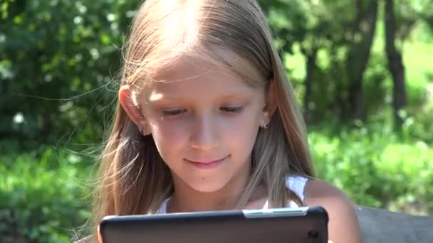 Kid Playing Tablet Swinging in Park, Girl Uses Smartphone in Garden, Child Relaxing Outdoor in Nature