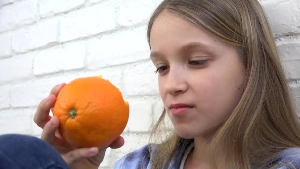 Kid Eating Oranges Fruits at Breakfast, Child Smelling Healthy Food, Blonde Girl in Kitchen, Children Healthcare