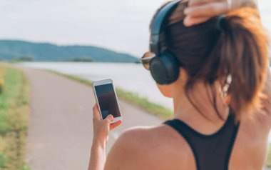 Young teenager girl starting jogging and choosing favorite music composition to listening using smartphone and  wireless headphones.
