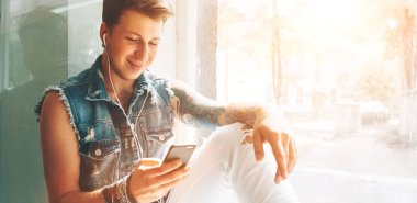 Young man listen music with headphones and smartphone sitting on windowsill
