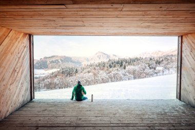 Man sits in wooden hangar wit view on snowy  mountain valley