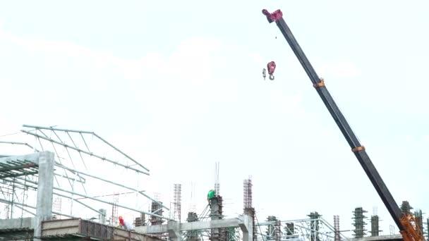 Stavební průmysl inženýra obchodního konceptu s pracovníkem stojící a pracuje na budování převahu a ocelovou tyč s jeřábu na staveništi na modrém pozadí oblohy a mraky.
