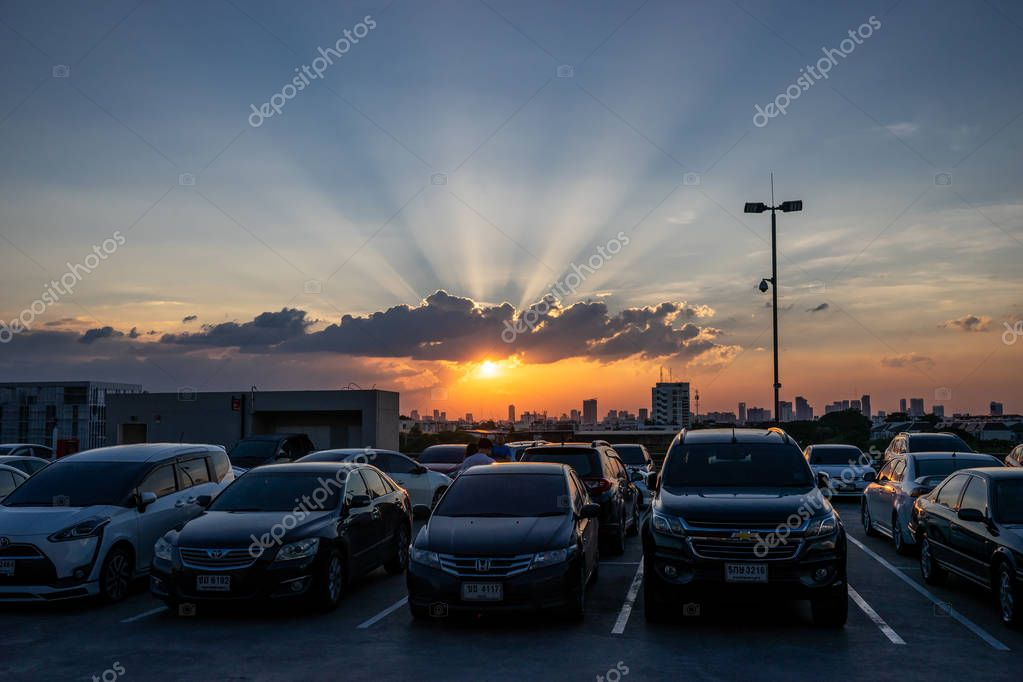The sun is setting on twilight dramatic sky, over cars, on top roof carpark in Bangkok. Thailand. 27/10/18