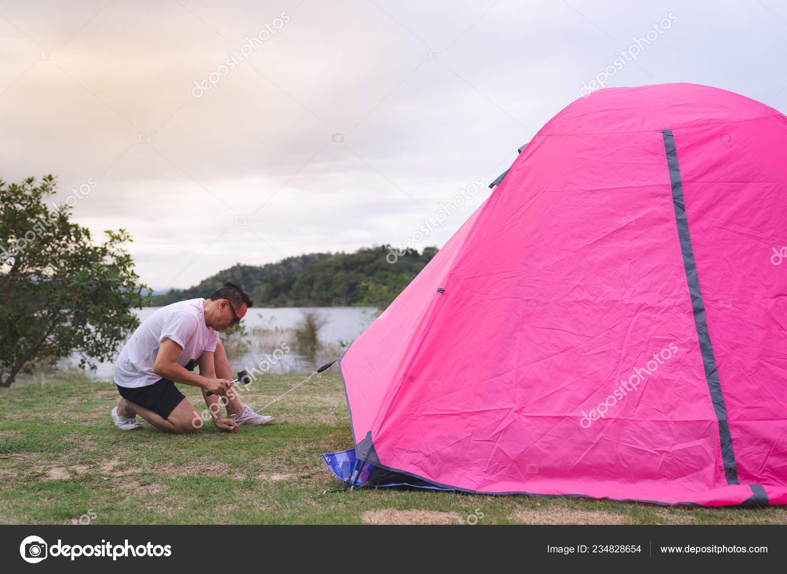 An Asian man in white t shirt setting pink tent at c&groundu2013 stock image & Asian Man White Shirt Setting Pink Tent Campground u2014 Stock Photo ...