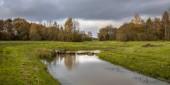 Pohled na meandrující potok v údolí malé řeky v Drenthe, Nizozemsko