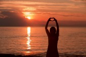 Fotografia Sagoma di donna mani a forma di cuore con tramonto magico colorato rosso