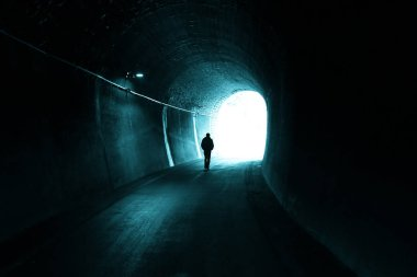 Man walks alone in dark tunnel with light in the end