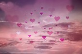 Pink colored blurry hearts fly over defocused sunset sky background.