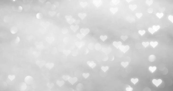 Kouzelné bílé srdce letící pomalu spadnout na pozadí rozmazané stříbrné bokeh reflexe.
