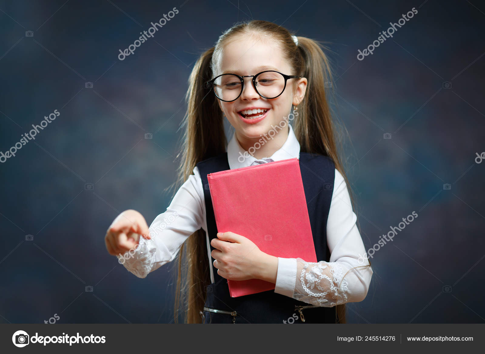 9aa0d1b3d455 Happy Little Schoolgirl in Uniform Hold Book Tight and Shows Finger At.  Cute Intelligent Girl Wear Big Glasses and Traditional Black and White  Outfit.