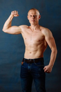 Portrait of strong healthy handsome Athletic Man Fitness Model wearing jeans posing near dark blue wall.