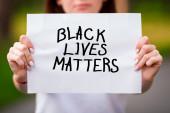 Fotografie Unscharfes Mädchen im Freien hält einen Zettel mit den Worten BLACK LIVES MATTERS vor sich