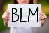 Fotografie Verschwommenes kaukasisches Mädchen im Freien mit BLM-Papierzeichen vor sich