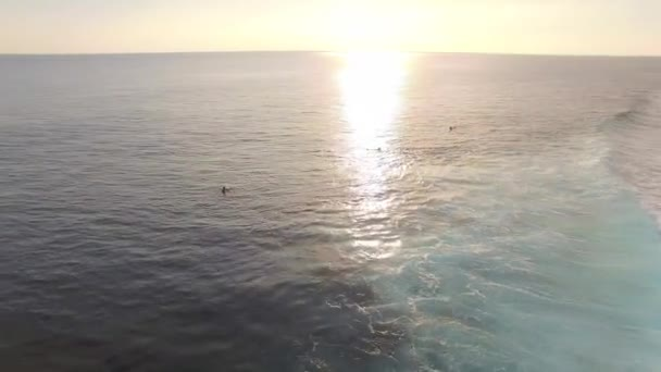 group of surfers in Indonesian bay at sunset