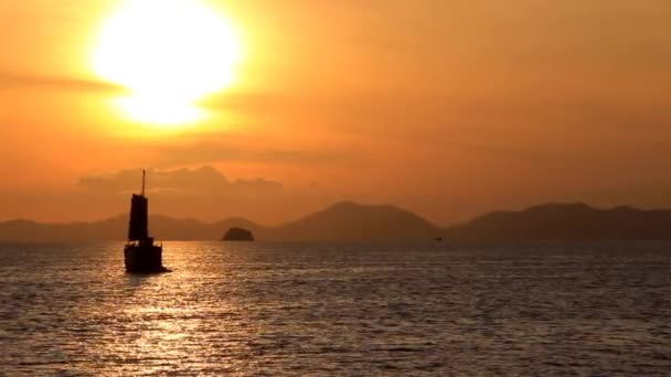 sailboat is floating on the sea, as the sun sets on the horizon