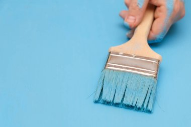 Male hand covered in paint, holding a paint brush on a wooden ba