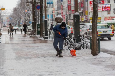 Otaru, Japan - December 25, 2017: Unidentified pedestrians walk in Sapporo City during winter season and road all cover by snow in Sapporo City, Hokkaido Japan.