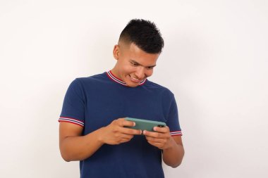 Handsome young man  holding in hands smartphone, playing video games or chatting