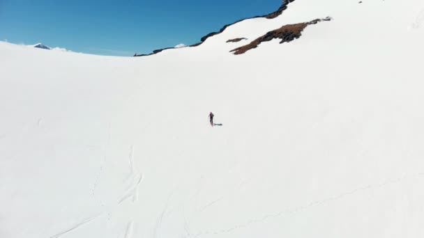 Aerial: flying over hiker walking towards snowy mountain top, ski touring mountaineering snow mountain, panoramic view on the alps, conquering adversity, achieving success