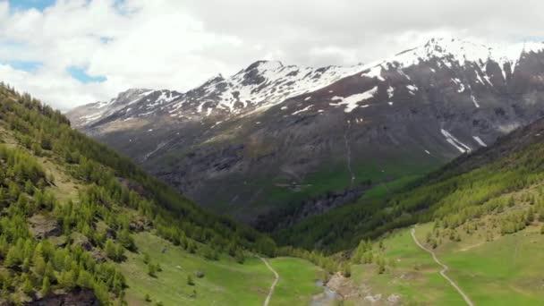Anténa: létání nad alpské údolí, creek v rokli, malebný vodopád zelené lesní zasněžené horské pásmo a dramatické silniční